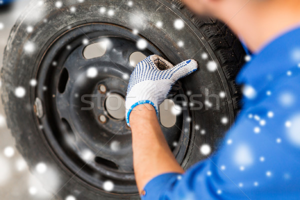 close up of auto mechanic with car tire Stock photo © dolgachov