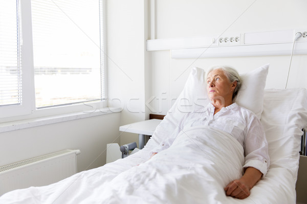 sad senior woman lying on bed at hospital ward Stock photo © dolgachov
