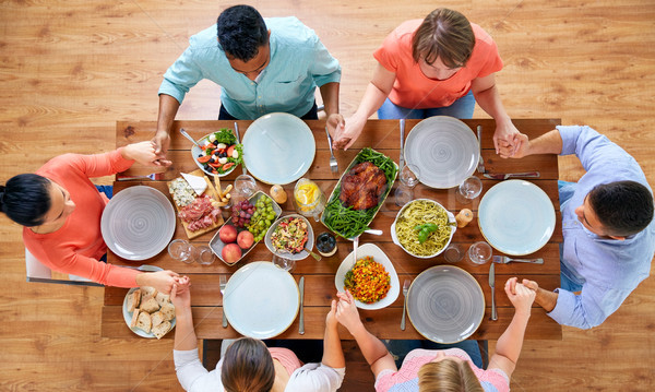 group of people at table praying before meal Stock photo © dolgachov