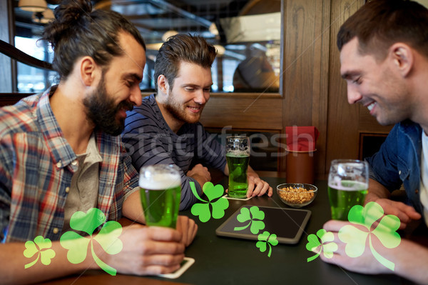 friends with tablet pc and green beer at pub Stock photo © dolgachov