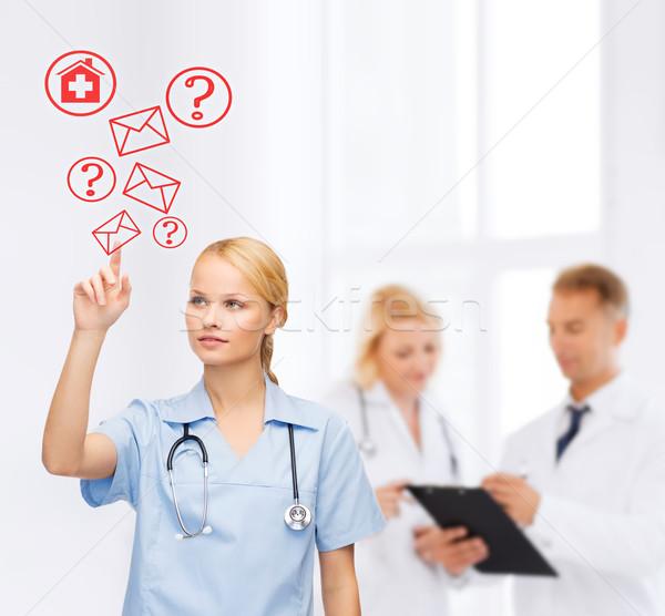 focused doctor or nurse pointing to red envelope Stock photo © dolgachov