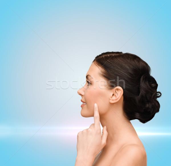 Sorridente mulher jovem indicação bochecha saúde Foto stock © dolgachov