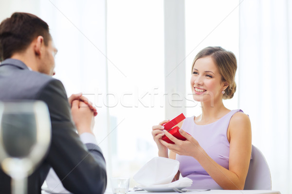 excited young woman looking at boyfriend with box Stock photo © dolgachov