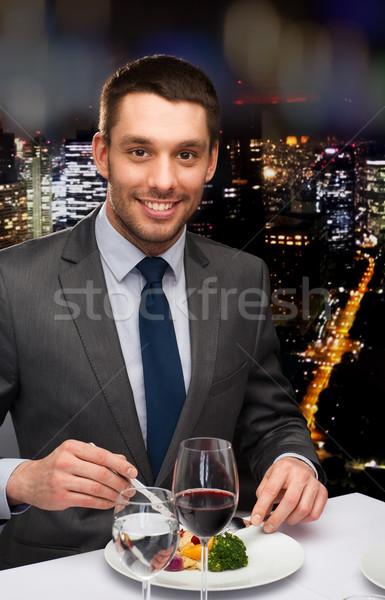 Sorridente homem alimentação restaurante pessoas Foto stock © dolgachov