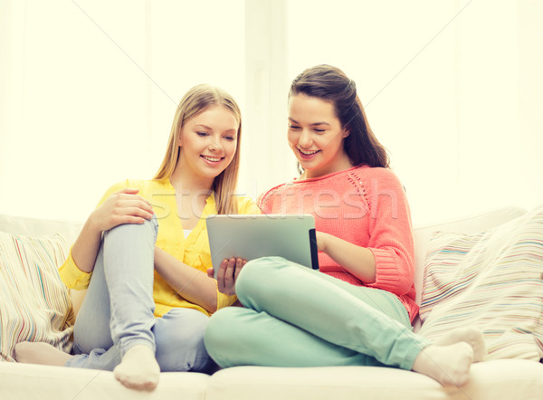 Stock photo: two smiling teenage girls with tablet pc at home