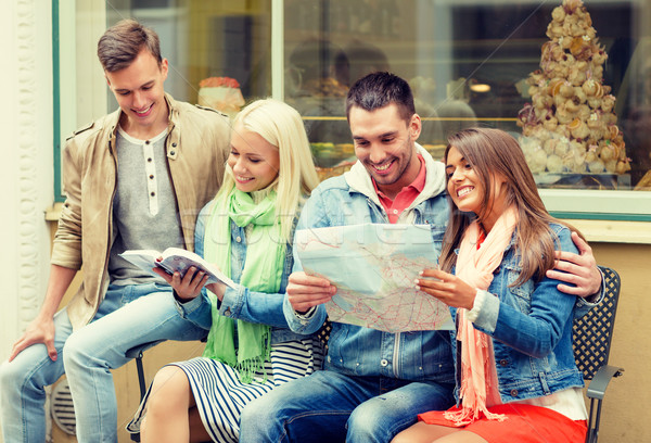 group of friends with guide and map exploring town Stock photo © dolgachov