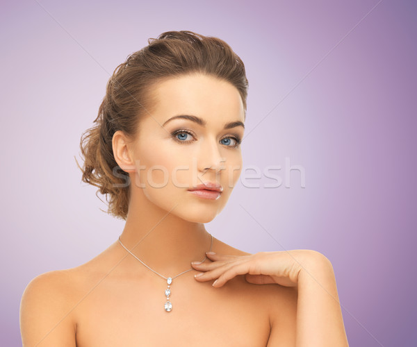 beautiful young woman with shiny diamond pendant Stock photo © dolgachov