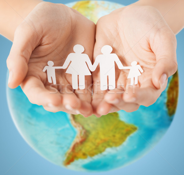 human hands holding paper family over earth globe Stock photo © dolgachov
