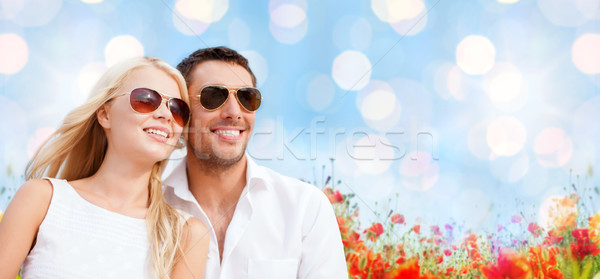 happy couple in shades over poppy field background Stock photo © dolgachov
