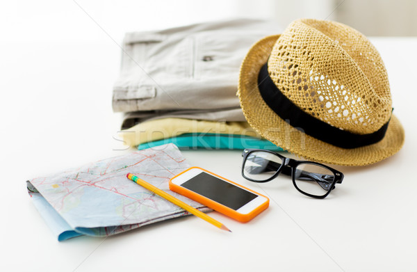 close up of summer clothes and travel map on table Stock photo © dolgachov