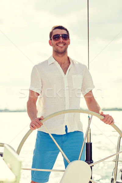 Jonge man zonnebril stuur jacht vakantie vakantie Stockfoto © dolgachov