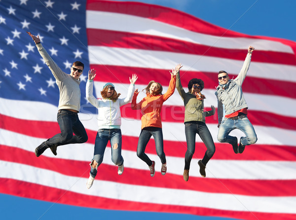 smiling friends in sunglasses jumping high Stock photo © dolgachov