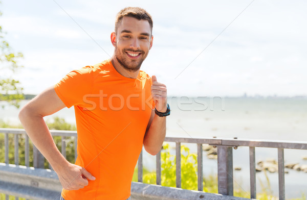 smiling young man running at summer seaside Stock photo © dolgachov
