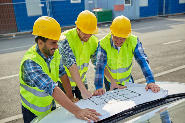 close up of builders with blueprint on car hood Stock photo © dolgachov