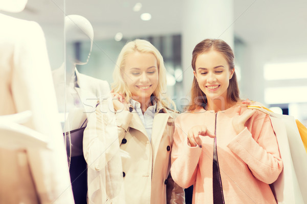 Stock photo: happy young women with shopping bags in mall