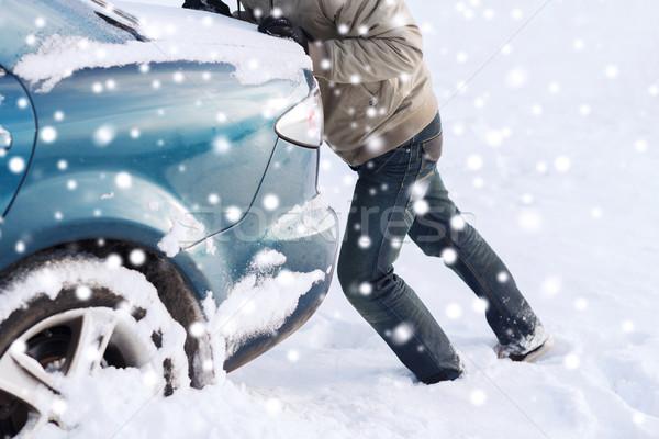 Primo piano uomo spingendo auto bloccato neve Foto d'archivio © dolgachov