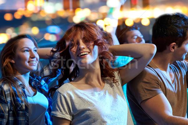 happy friends dancing at night club Stock photo © dolgachov