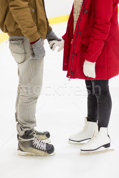 close up of happy couple skating on ice rink Stock photo © dolgachov