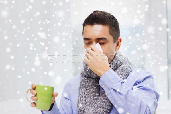 Człowiek grypa pitnej herbaty dmuchanie nosa Zdjęcia stock © dolgachov