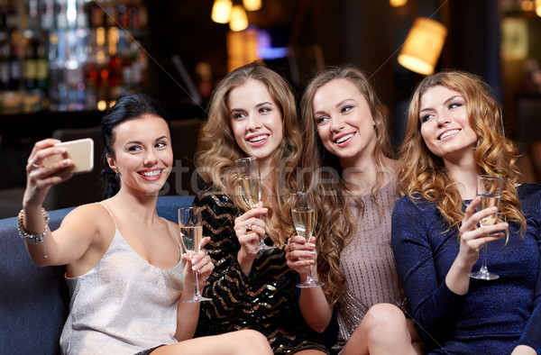 women with champagne taking selfie at night club Stock photo © dolgachov