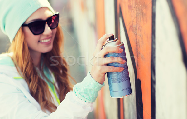 close up of woman with spray paint making graffiti Stock photo © dolgachov
