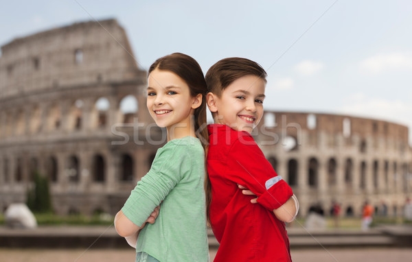 happy boy and girl standing over coliseum in rome Stock photo © dolgachov
