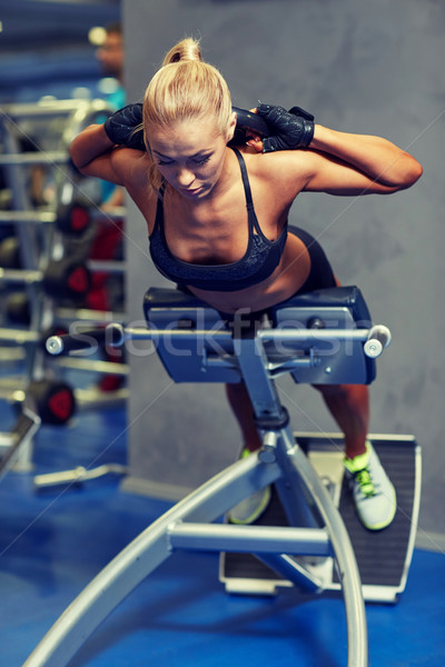 young woman flexing back muscles on bench in gym Stock photo © dolgachov