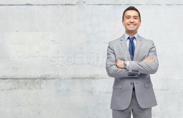 Szczęśliwy biznesmen garnitur konkretnych ściany ludzi biznesu Zdjęcia stock © dolgachov