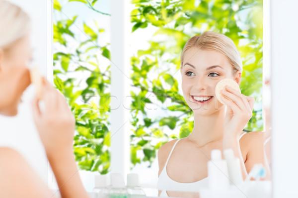 Jeune femme lavage visage éponge salle de bain beauté Photo stock © dolgachov