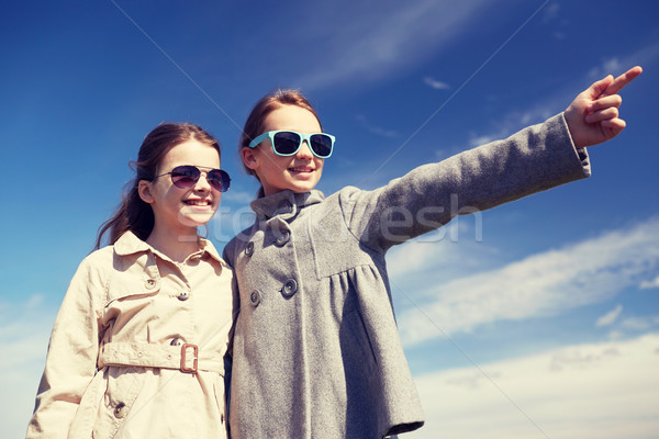 happy little girls hugging and pointing finger Stock photo © dolgachov