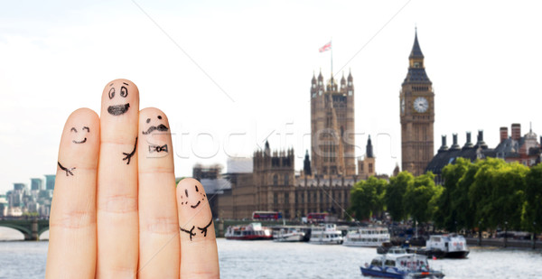 close up of fingers with smiley faces over london Stock photo © dolgachov