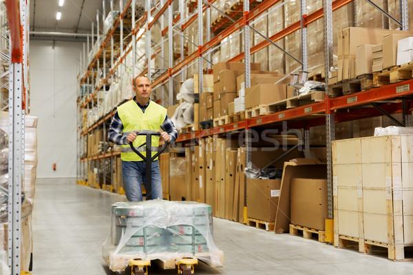 man carrying loader with goods at warehouse Stock photo © dolgachov