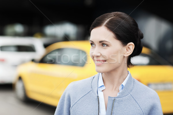 smiling woman over taxi station or city street Stock photo © dolgachov