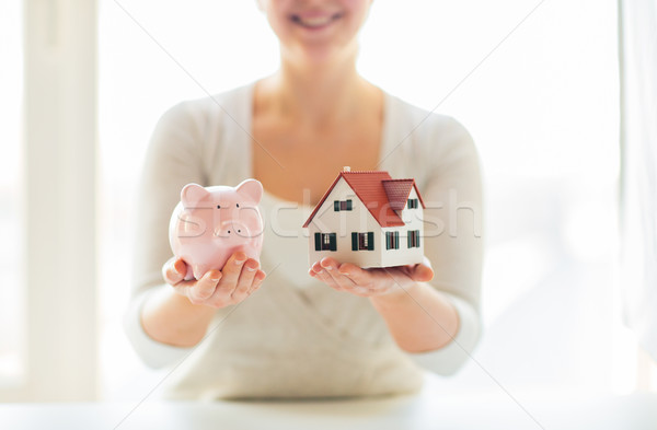 close up of woman with house model and piggy bank Stock photo © dolgachov