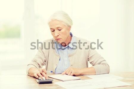 senior woman with glucometer checking blood sugar Stock photo © dolgachov