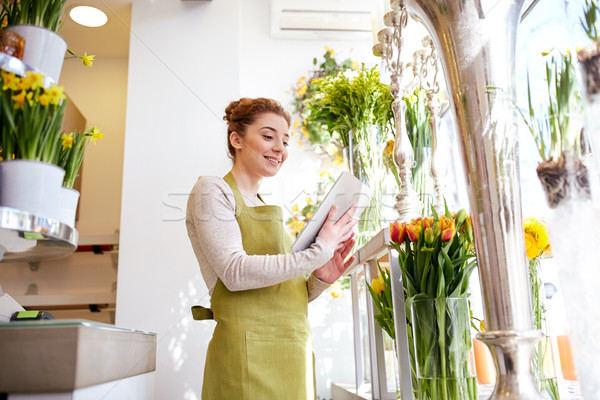 woman with tablet pc computer at flower shop Stock photo © dolgachov