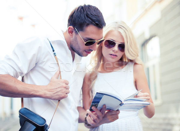 couple with tourist book in the city Stock photo © dolgachov