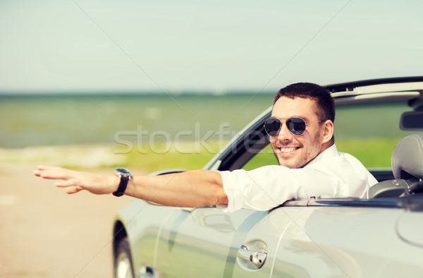 happy man driving cabriolet car and waving hand Stock photo © dolgachov