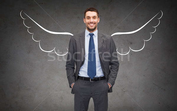happy businessman with angel wings over gray Stock photo © dolgachov