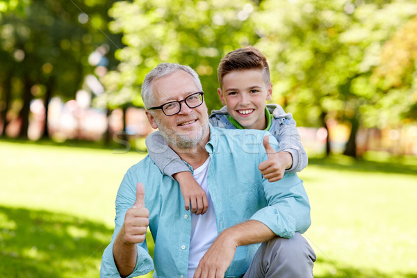 grandfather and boy showing thumbs up at summer Stock photo © dolgachov