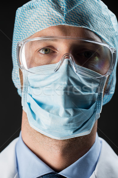 close up of scientist in goggles, mask and hat Stock photo © dolgachov