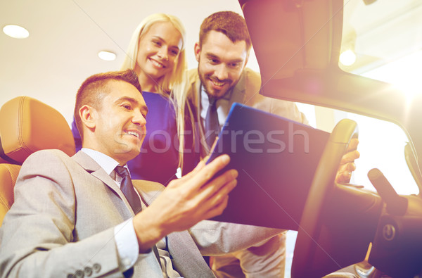 happy couple with car dealer in auto show or salon Stock photo © dolgachov
