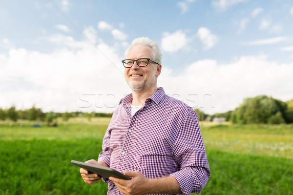 senior man with tablet pc computer at county Stock photo © dolgachov