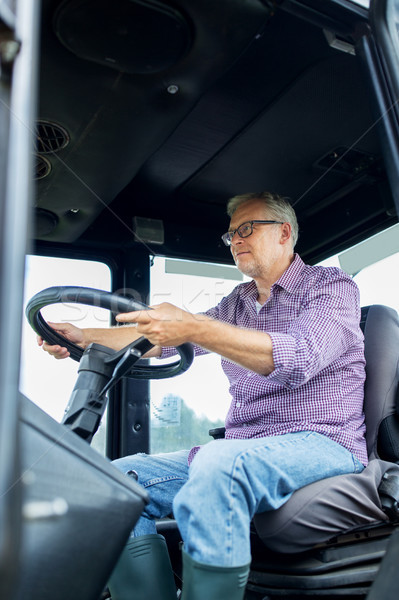 senior man driving tractor at farm Stock photo © dolgachov