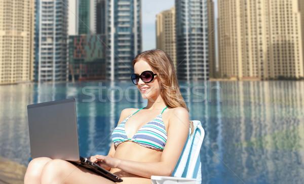 Donna laptop prendere il sole lounge spiaggia estate Foto d'archivio © dolgachov