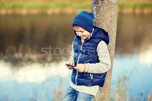 happy boy playing game on smartphone outdoors Stock photo © dolgachov