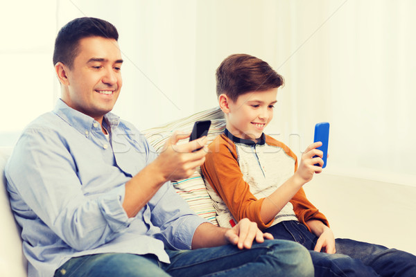happy father and son with smartphones at home Stock photo © dolgachov