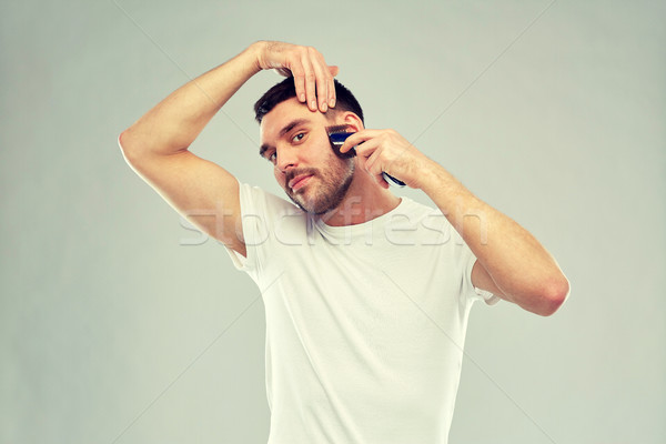smiling man shaving beard with trimmer over gray Stock photo © dolgachov