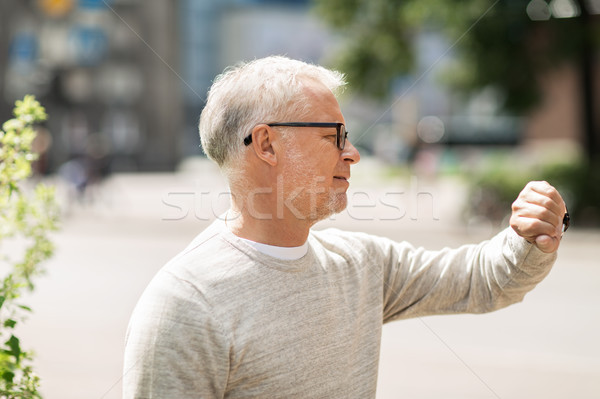 senior man checking time on his wristwatch Stock photo © dolgachov