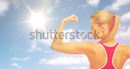 happy sporty woman showing biceps over sky and sun Stock photo © dolgachov